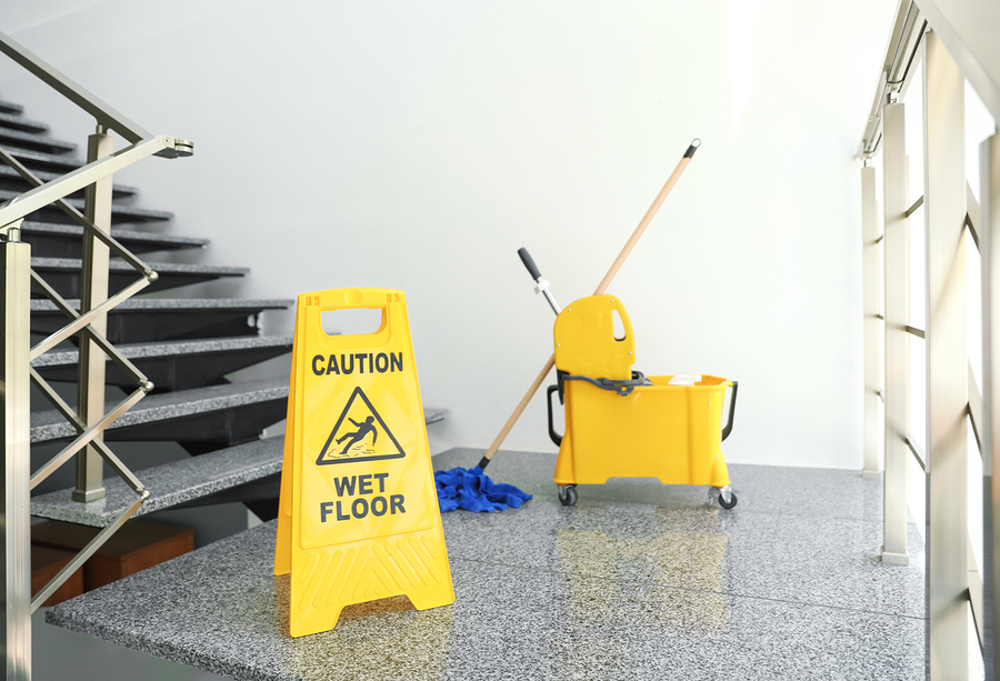 """safety sign with phrase """"caution wet floor"""" and mop bucket on stairs. cleaning tools"""